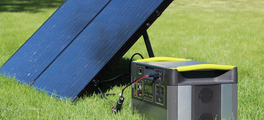 Goal Zero Yeti sitting in grass with a Renogy 100 watt solar panel