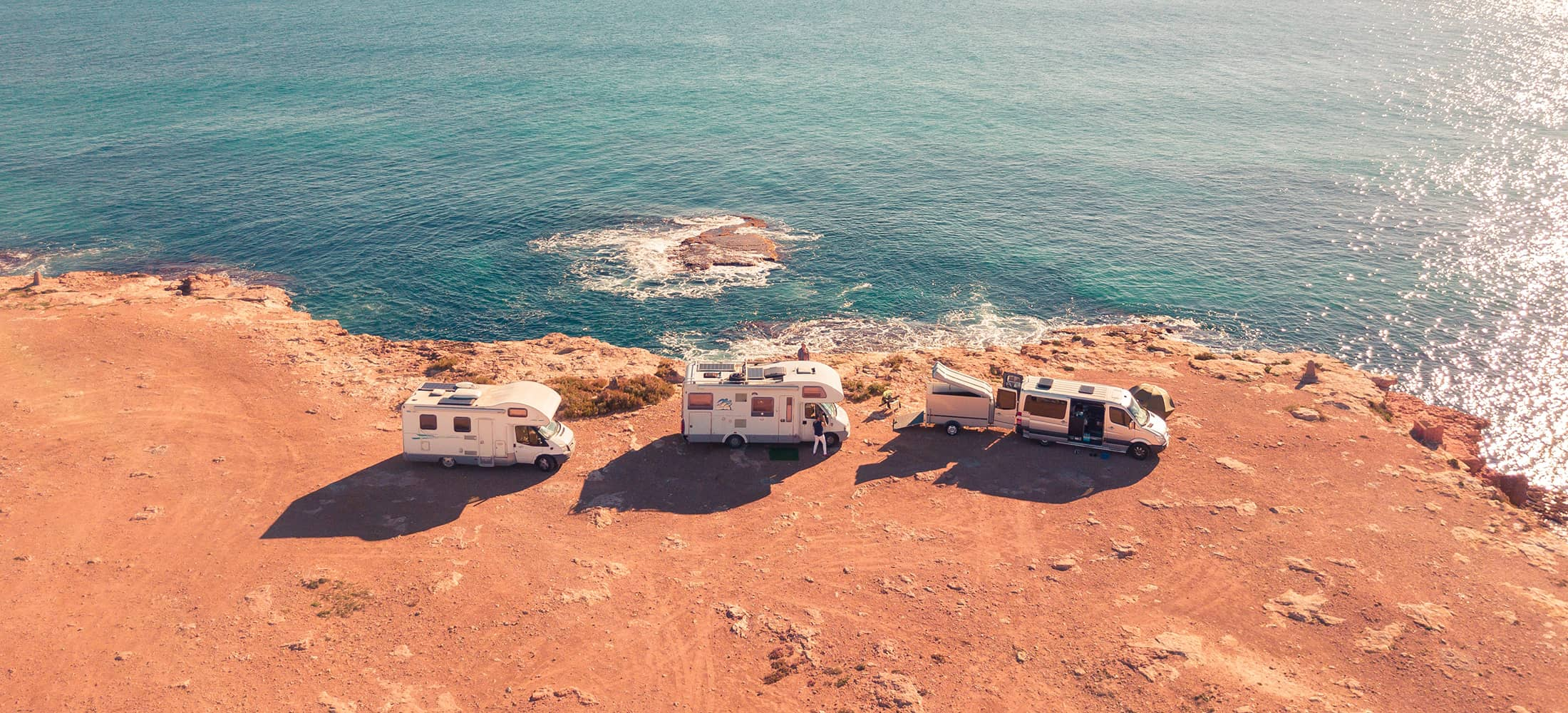 three campers near the ocean